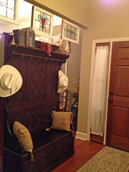 Heavily carved antique hall bench beneath the stained glass panels - and a great collection of cowboy hats! EuroLuxAntiques.com